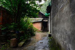 Alley between aged dwelling buildings after rain Royalty Free Stock Image