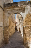 Alley with arch in Fes medina. Medieval street in Fes medina in Morocco Royalty Free Stock Images