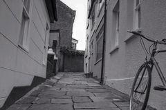 Alley and a bicycle. A narrow alley, houses and bycycle stock photo
