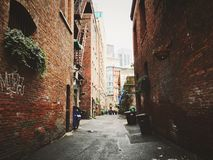 Alley Between Brown Bricked Buildings Stock Photo