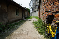 Alley between dilapidated houses and brick enclosure in sunny su Stock Images