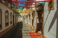 Alley with festive colorful decoration and old houses. Deserted alley with festive colorful decoration and old terraced houses, on sunny day at Portalegre. A stock images