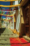 Alley with festive colorful decoration and old houses. Deserted alley with festive colorful decoration and old terraced houses, on sunny day at Portalegre. A royalty free stock photos