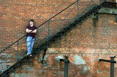 Alley Fire Escape. Young man stands on metal fire escape. He is sad and feeling hopeless to escape his life in the inner city Stock Photography