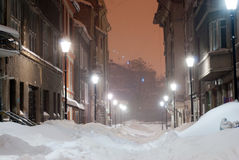 Alley full of snow by night. A small hidden alley covered by snow in the evening lights Royalty Free Stock Photo