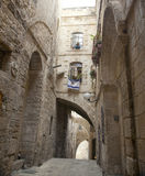 Old Jerusalem Alley. An alley in the Jewish quarter of the old city of Jerusalem, Israel. Hanging from the bottom window is an israel flag with the symbol of Stock Photo