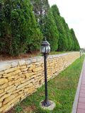Alley with lanterns. Tui and stone fence in the park stock photos
