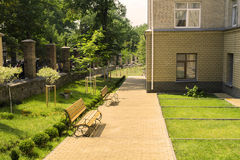 Alley with lawns, benches, trees and a metal fence Royalty Free Stock Images