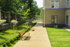 Alley with lawns, benches, trees and a metal fence Stock Photography