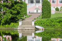 Alley leading to manorhouse and pond with pier in front Royalty Free Stock Photo