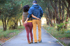 Alley of love. Man and woman are walking down the alley in the park, cuddling, holding hands in the pockets Stock Photo