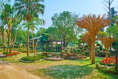 The Akha swing and bamboo sunshades in Mae Fah Luang garden, Doi Tung, Thailand. The alley of Mae Fah Luang garden is decorated with tall palm trees, flower beds stock photos