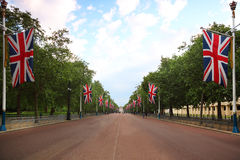 Alley Mall, Buckingham Palace are seen in distance. Alley Mall, Buckingham Palace are seen in the distance. Right and left of the mall hang British flags Stock Photos