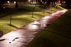 Alley at night. Road, alley or path wet from the rain and lighted by  street lamps on autumn night Royalty Free Stock Photo
