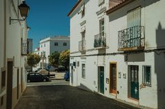Alley with old houses and deserted causeway. Narrow empty alley with old houses facade and deserted causeway on a sunny day at Campo Maior. A cute little town royalty free stock photo