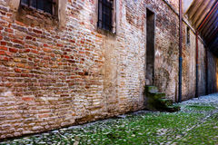 Alley in the old town. Dirty alley in the old town with pavement of porphyry cobblestones Stock Photography