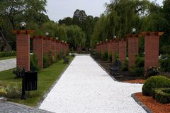 Alley in a park. Alley in park paved with white marble tiny stones Stock Image