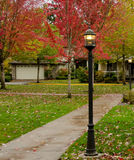 Alley with red maple foliage and street lights Royalty Free Stock Photography