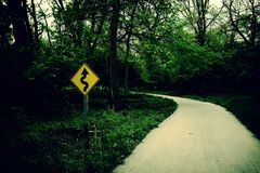 Alley with sign. Cross-processed alley curving to the left with yellow winding road sign Stock Images