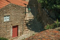 Alley on slope passing through old stone houses at Monsanto. Deserted alley on slope passing through old stone houses and leafy trees, in a sunny day at Monsanto royalty free stock image