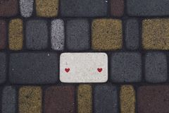 Alley from smoothly laid colored bricks. Fragment of the alley from smoothly laid colored bricks with two red hearts Royalty Free Stock Photos
