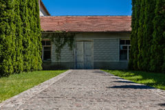 Alley of trees leading to the house with old doors Royalty Free Stock Photos