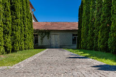 Alley of trees leading to the house with old doors Stock Images