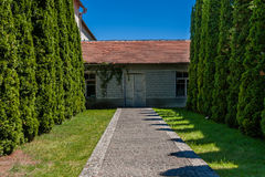 Alley of trees leading to the house with old doors Stock Photography