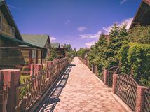 Resort alley. Alley in a tropical resort on a sunny day. decorative fence along the sidewalk. minimalistic houses with fir trees in the yard stock photos