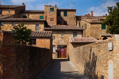 Alley with typical stone houses, San Quirico d`Orcia, Tuscany, Italy.  stock photography