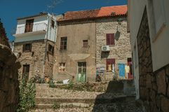 Alley and worn old house with clothes hanging to dry. Deserted alley and worn old house facade with clothes hanging to dry in front, in a sunny day at Belmonte stock image