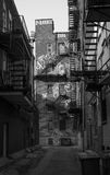 Alleyway with graffiti and fire escapes Stock Photos