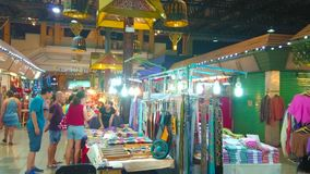 Alleyway of Night Market, Chiang Mai, Thailand. CHIANG MAI, THAILAND - MAY 2, 2019: People choose interesting pieces of clothes and accessories in stalls of stock footage