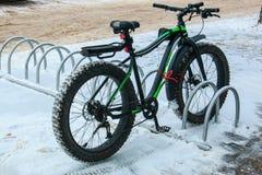 Allez à vélo avec un caoutchouc large dans le parking près du magasin dans la ville pendant l'hiver photos libres de droits