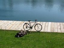 Allez à vélo et homme de détente sur l'herbe près d'un étang Image libre de droits
