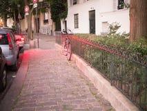 Allez à vélo le penchement contre la barrière de fer, baignée dans la lumière rouge du trafic, Montmartre, Paris, début de soirée Photos stock