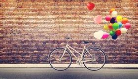 allez à vélo le vintage avec le ballon de coeur sur la ville urbaine de route Photos stock
