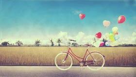Allez à vélo le vintage avec le ballon de coeur sur le champ de ferme et le ciel bleu Image stock