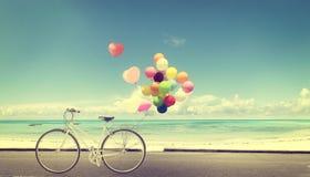 Allez à vélo le vintage avec le ballon de coeur sur le ciel bleu de plage Image libre de droits