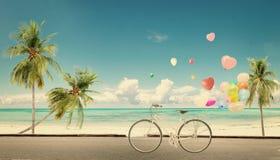 Allez à vélo le vintage avec le ballon de coeur sur le ciel bleu de plage Image stock