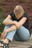 Allgemeine Ansicht der frustrierten Frau sitzend auf dem hölzernen Brett Stockfoto