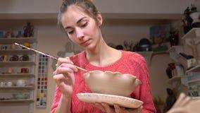 Allgemeine Ansicht eines weiblichen Ceramist, der das Tongefäß glatt macht, umrandet unter Verwendung der Quaste in der Tonwarenw