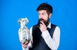 Allgemeine Einsparungensspitzen Hippie-Griffglas des Mannes b?rtiges voll Bargeld Halten von Bargeldfragen Gesch?ftsmann mit sein stockbilder