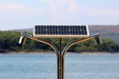 Allgemeine Verdoppelungdusche auf dem Seestrand, der mit kleinem Sonnenkollektor auf Spitze und Wald angetrieben wurde, bedeckte  lizenzfreies stockbild