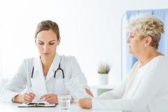 Allgemeiner Doktor, der mit Patienten sich berät lizenzfreie stockbilder