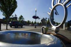 Allgemeiner Trinkbrunnen auf Straße mit Autos und Grün treen an Stockbilder