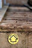 Allgemeines Fußwegenzeichen auf hölzernem Gehweg Stockfotografie