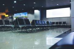 Allgemeines Handelsbrett bei der Aufwartung der Flughafenhalle mit leeren Stühlen Lizenzfreie Stockfotografie
