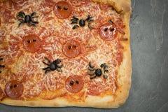 Allhelgonaafton-Themed pizza med Spindel-formade peperoni och oliv C Arkivbilder