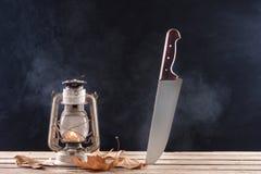 Allhelgonaaftonbakgrund av den stora kniven som stickas i träskrivbord och gammal gaslampa arkivfoton